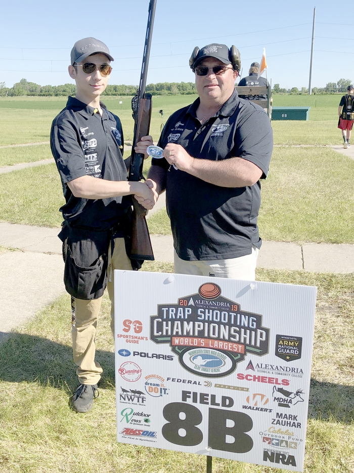 Seanne Prigge receives a 25-straight patch from Head Coach Chad Loewen at the Minnesota State Trapshooting Championship held in Alexandria.